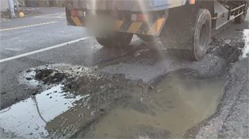 土石沿路灑...沙塵飛揚  原來是砂石車後車斗門閂壞了