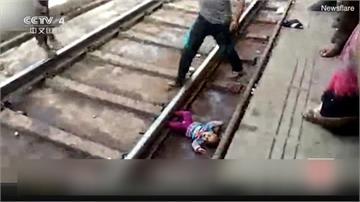 驚險瞬間!印度女嬰摔落鐵道 火車疾駛竟無傷